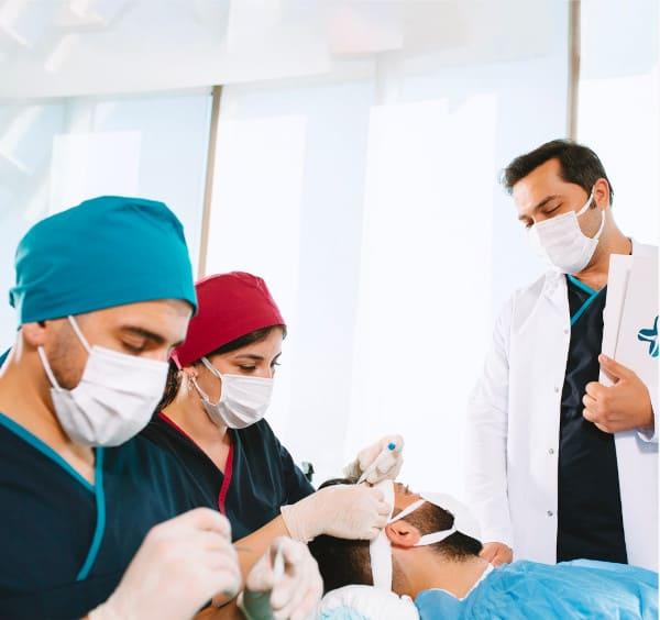 Dr. Balwi discutant avec un patient pendant une greffe de cheveux DHI