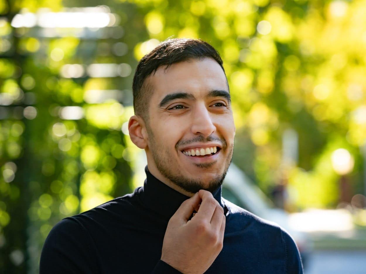 Junger Mann mit vollem Haar lächelt.