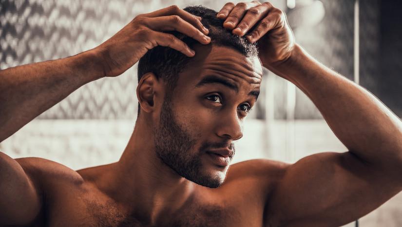 Mann betrachtet seinen Haarausfall im Spiegel.