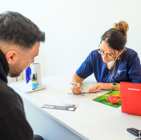 Beratungsgespräch zwischen einem Teammitglied und einem Patienten bei Elithair in München