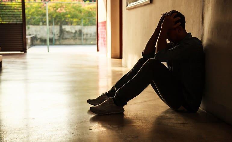 Mann sitzt im Dunkeln am Boden mit Händen am Kopf, verzweifelt wegen Haarausfall am Bart