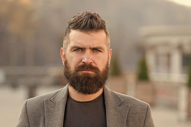 Mann mit Vollbart im Anzug nach Haartransplantation wegen Haarausfall am Bart