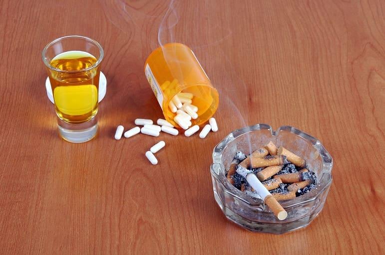 Whiskey im Glass, Pillen und Zigaretten auf einem Holztisch